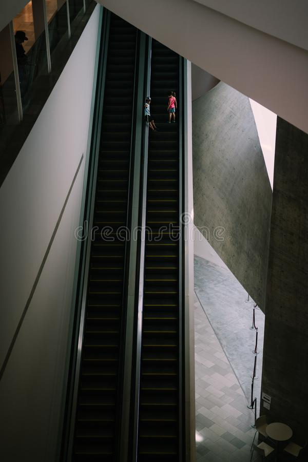 Two small children going up the escalator alone. royalty free stock photography