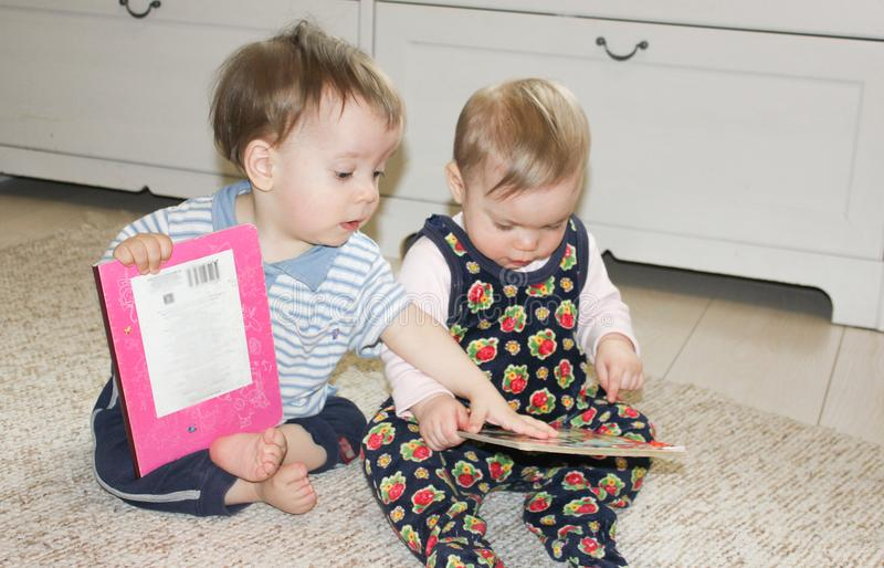 Two small children sit on the floor and read books. Girl and boy royalty free stock image