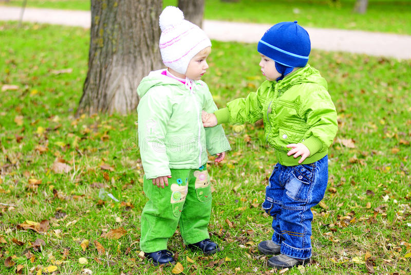 Two small children sit on a green clearing. With yellow leaves stock images