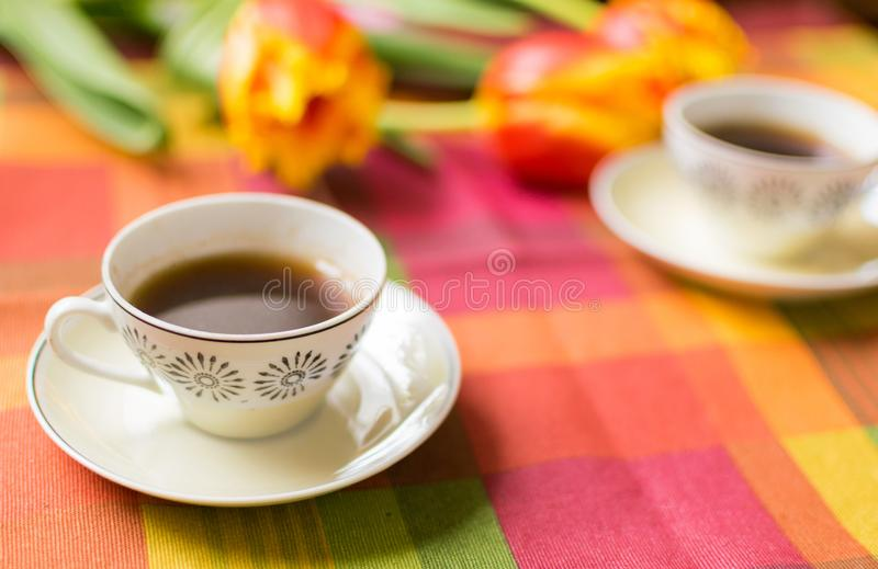 Two small cups of coffee on the saucers on the table with tulips. stock photos
