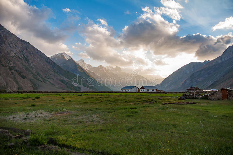 Two small farm houses in lush green valley surrounded by high mountains during sunrise royalty free stock photography