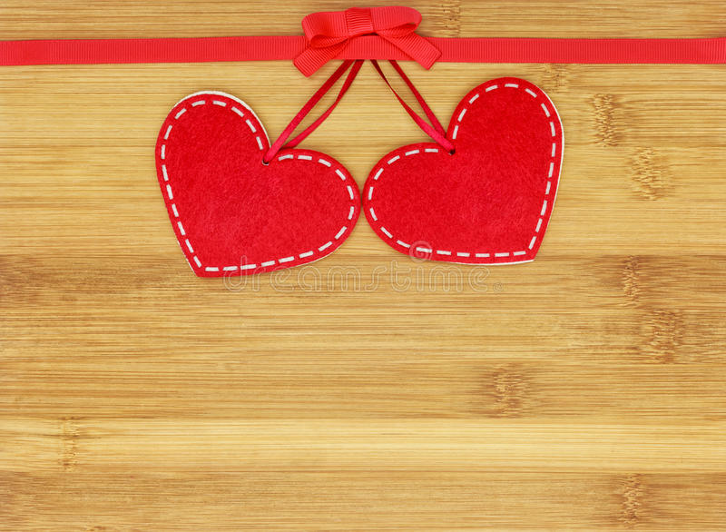 Two small felt hearts in the center of wooden background stock photography