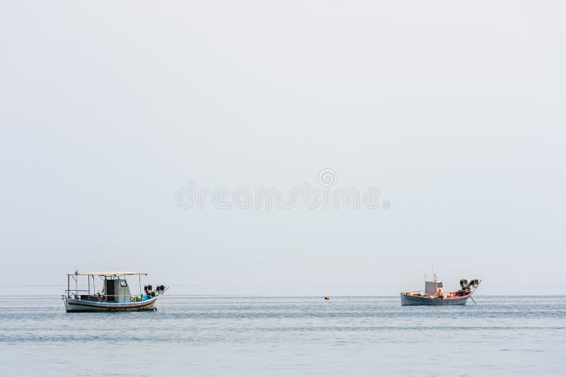 Two small fishing boat at sea surface stock photo