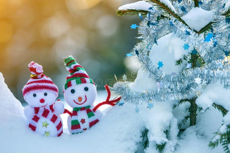 Two small funny toys baby snowman in knitted hats and scarves in deep snow outdoors near pine tree branch. Happy New Year and. Merry Christmas greeting card stock photography