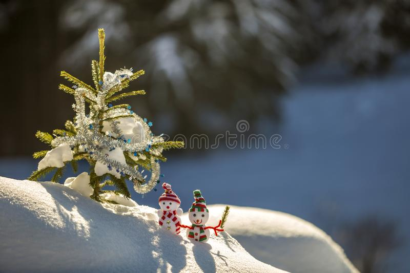 Two small funny toys baby snowman in knitted hats and scarves in deep snow outdoors near pine tree branch. Happy New Year and. Merry Christmas greeting card stock image