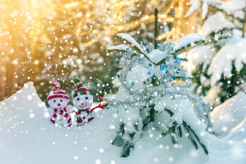 Two small funny toys baby snowman in knitted hats and scarves in deep snow outdoors near pine tree branch. Happy New Year and. Merry Christmas greeting card stock images