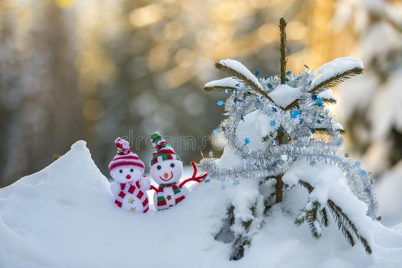 Two small funny toys baby snowman in knitted hats and scarves in deep snow outdoors near pine tree branch. Happy New Year and. Merry Christmas greeting card stock photos