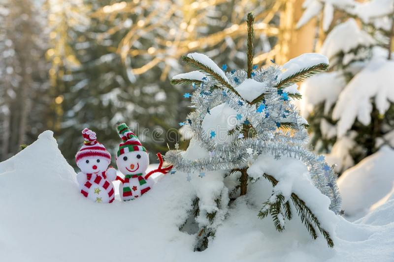 Two small funny toys baby snowman in knitted hats and scarves in deep snow outdoors near pine tree branch. Happy New Year and. Merry Christmas greeting card stock photo