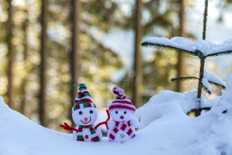 Two small funny toys baby snowman in knitted hats and scarves in deep snow outdoors near pine tree branch. Happy New Year and. Merry Christmas greeting card royalty free stock photo