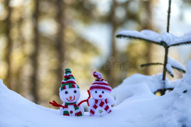Two small funny toys baby snowman in knitted hats and scarves in deep snow outdoors near pine tree branch. Happy New Year and. Merry Christmas greeting card royalty free stock images