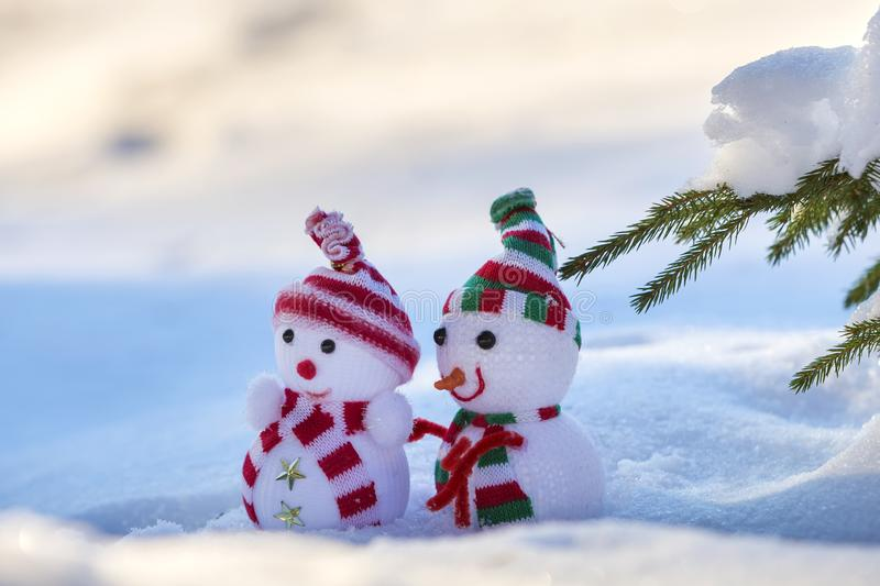 Two small funny toys baby snowman in knitted hats and scarves in deep snow outdoors near pine tree branch. Happy New Year and. Merry Christmas greeting card royalty free stock photography