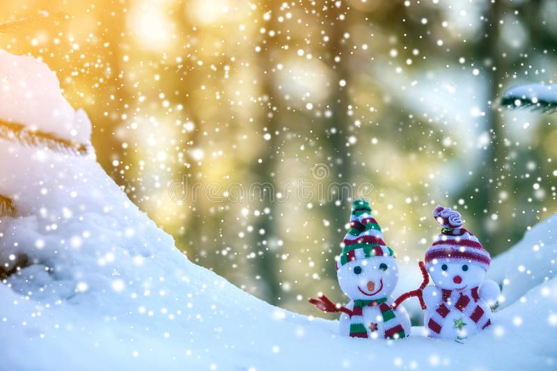 Two small funny toys baby snowman in knitted hats and scarves in deep snow outdoors near pine tree branch. Happy New Year and. Merry Christmas greeting card royalty free stock image
