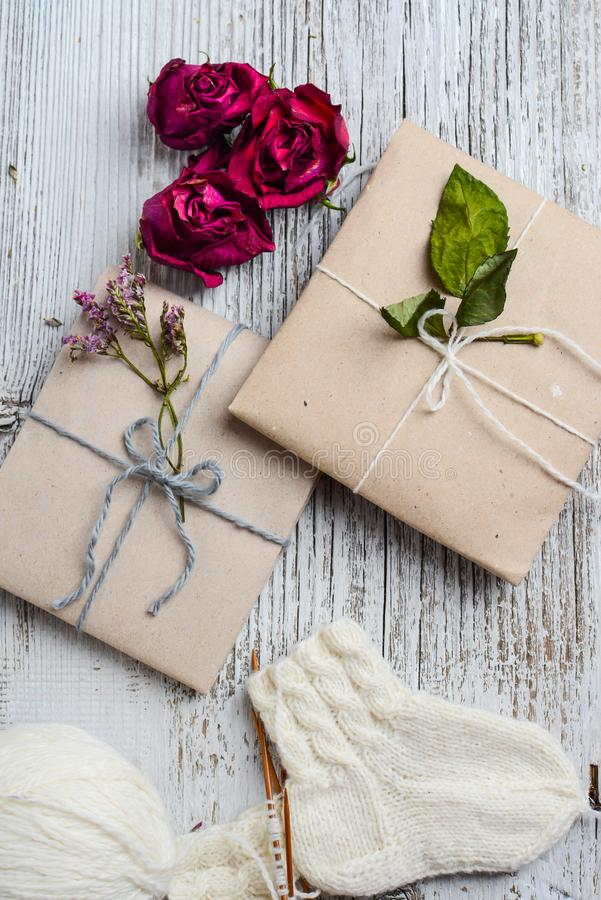 Two small gifts wrapped in ecologic paper, old wooden white table and vintage handmade sock royalty free stock photos