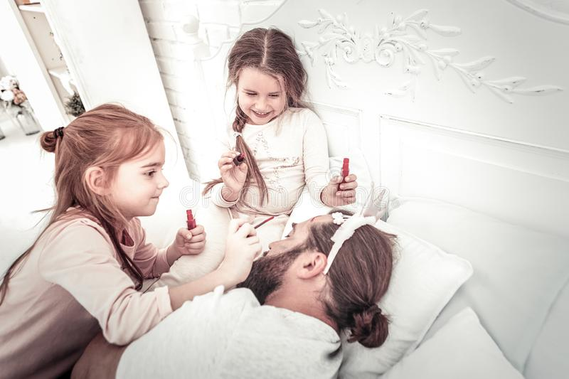 Two small girls painting fathers face while he still sleeping royalty free stock image