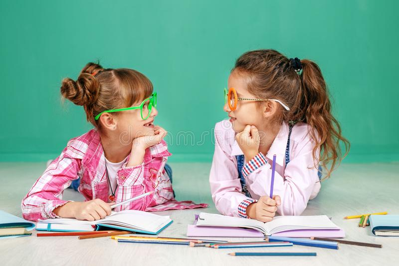 Two small girls speak and teach homework. The concept of childhood, learning, friendship, family, school, lifestyle. stock photography