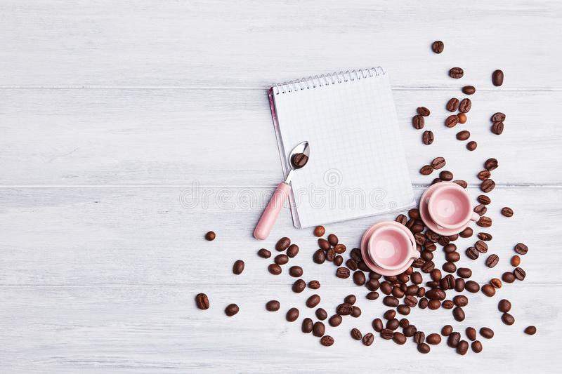 Two small pink cups on the table with a spoon, notepad and scattered coffee beans on a white wooden background. Invitation or greeting card. Top view. Meeting royalty free stock photography