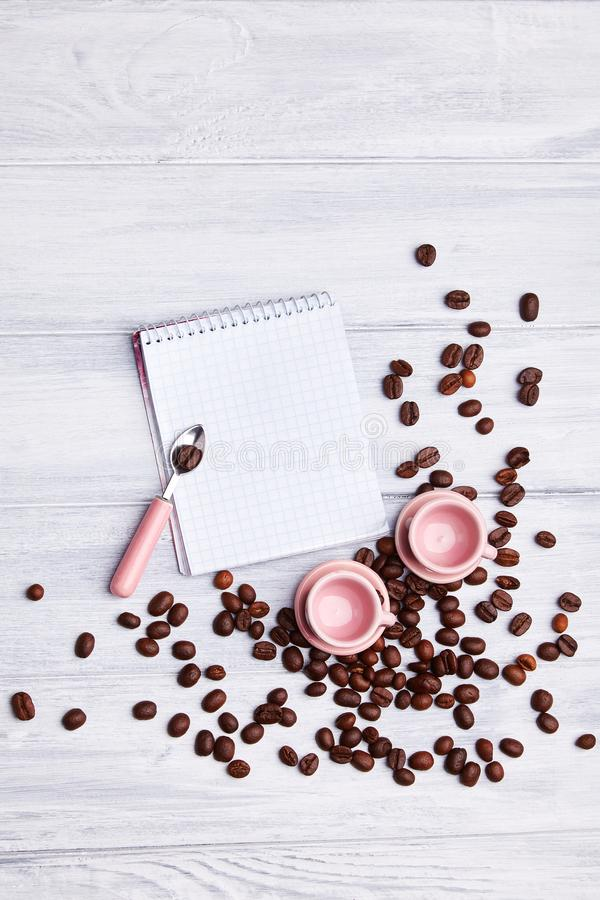 Two small pink cups on the table with a spoon, notepad and scattered coffee beans on a white wooden background. royalty free stock images
