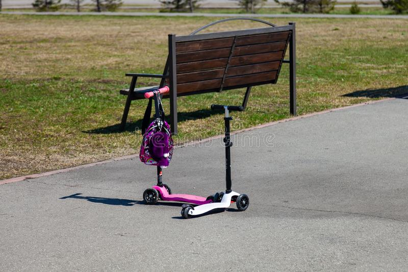 Two small pink and white children`s scooters are standing nearby in the park near the bench and the green lawn in anticipation of. Children for a summer walk on stock photography