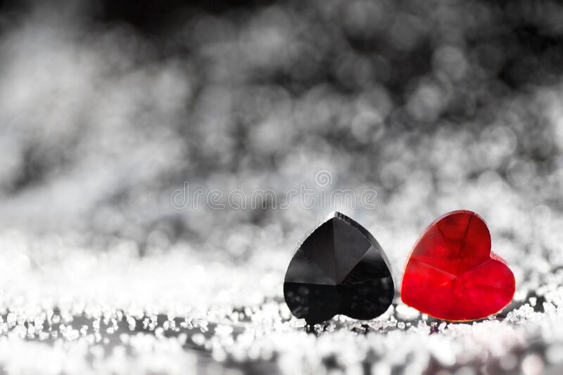 Two small red and black plastic hearts lying next to each other with beautiful silver bokeh effects and a copy space for text. Two small plastic hearts of red royalty free stock photography