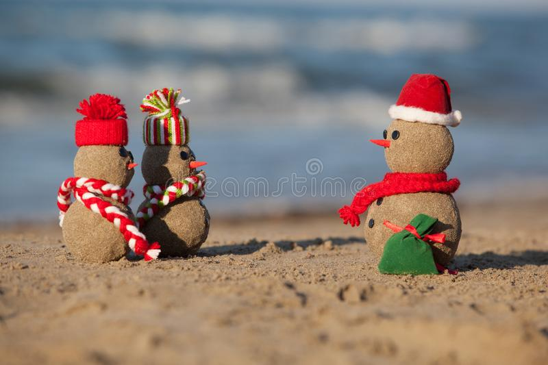 Two small sandy snowmen and santa at tropical beach. stock image