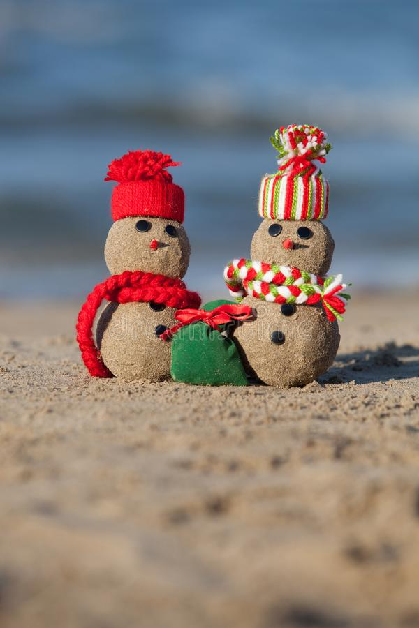Two small sandy snowmen at tropical beach. royalty free stock photo