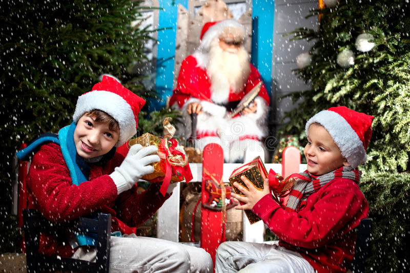 Two small Santa Clauses show satisfied their gifts. In a snow day stock image
