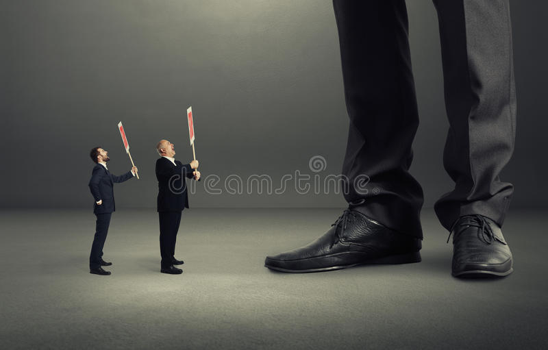 Two small screaming businessmen. Holding placard and looking up at big legs over dark grey background stock photos