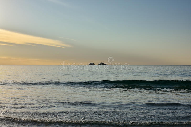 Two small silhouetted islands stock image