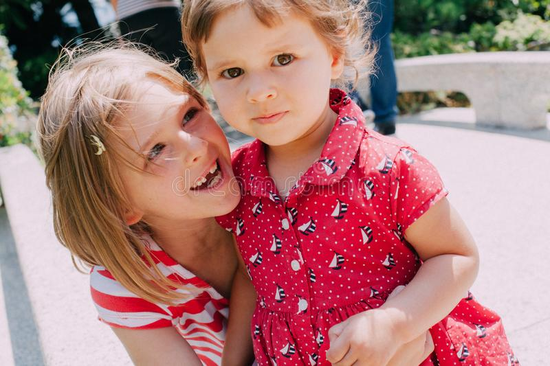 Two small sisters laugh and hug royalty free stock photo