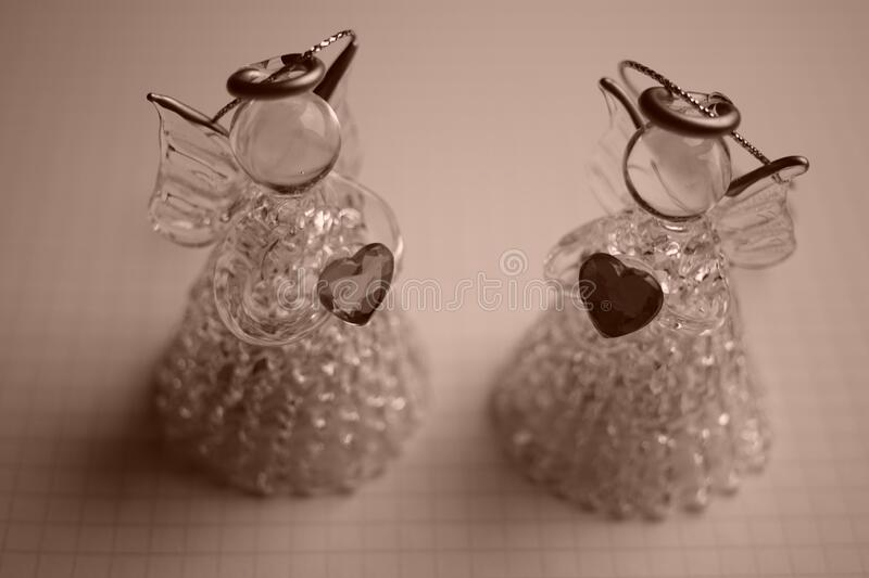 Two small statue of an angel with a heart in his hands on a paper in a cage.  royalty free stock photography