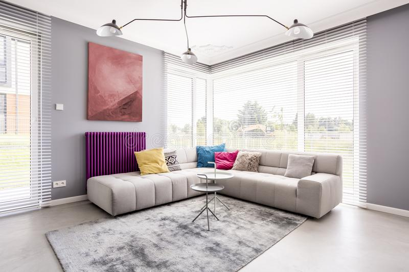 Two small tables on carpet. Two small tables standing on a soft, grey carpet by the sofa in the corner of a living room and an abstract painting on the wall royalty free stock photo