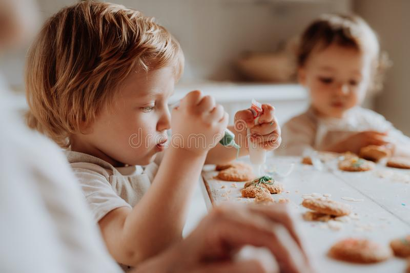 Two small toddler children sitting at the table, decorating and eating cakes at home. Two happy small toddler children sitting at the table, decorating and royalty free stock photo