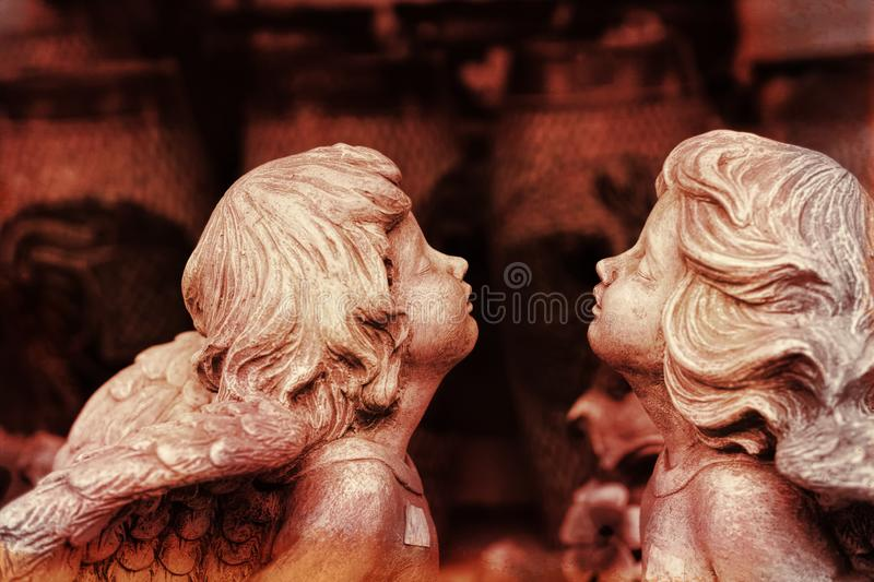 Two small kissing angels with closed eyes. Two small and young kissing angels with closed eyes royalty free stock photos