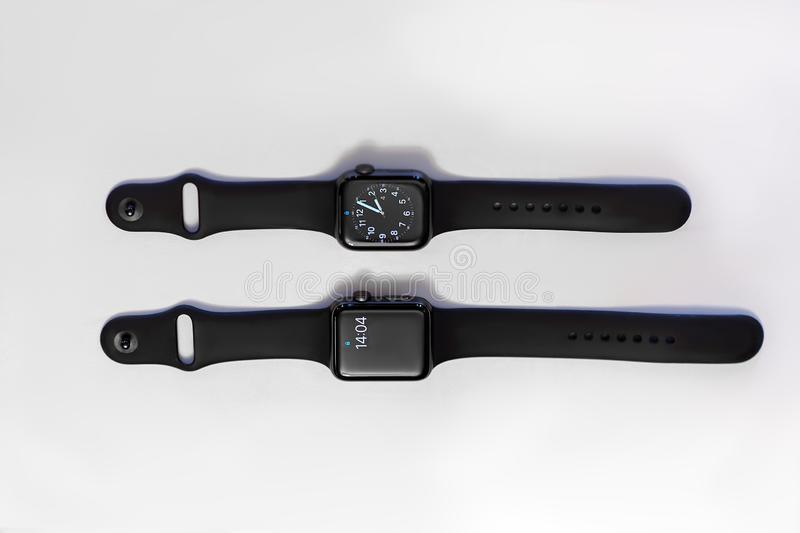 Two smart electronic watches on white background, with equal time on the screens. royalty free stock photography