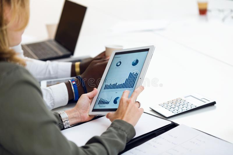 Two smart young businesspeople working with digital tablet on coworking place. Close up of two smart young businesspeople working with digital tablet on stock images