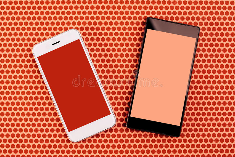 Two smartphones with blank screen, mock up copy space. Two smartphones with blank screens as mock up copy space, top view of mobile phones over dotted background stock image