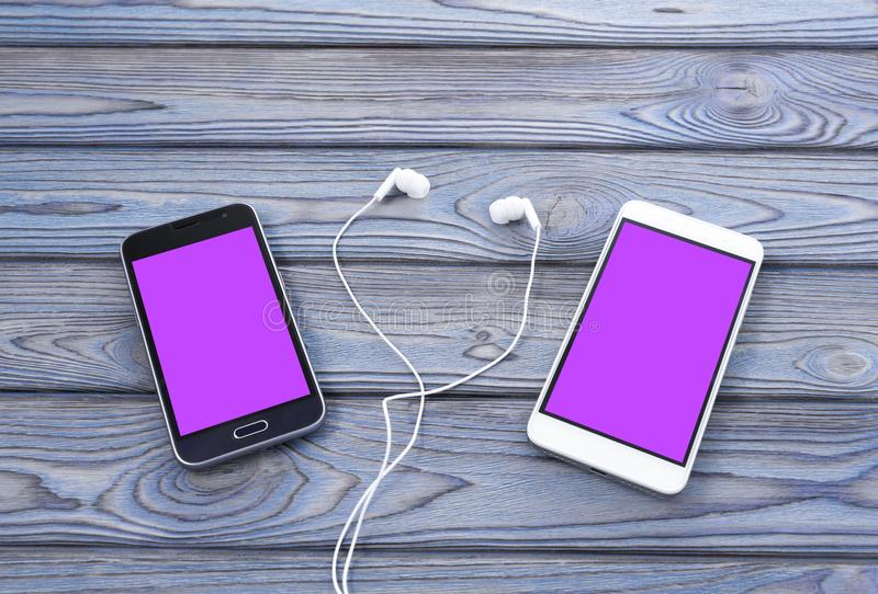 Two smartphones with a pink screen, headphones. On a wooden background royalty free stock images