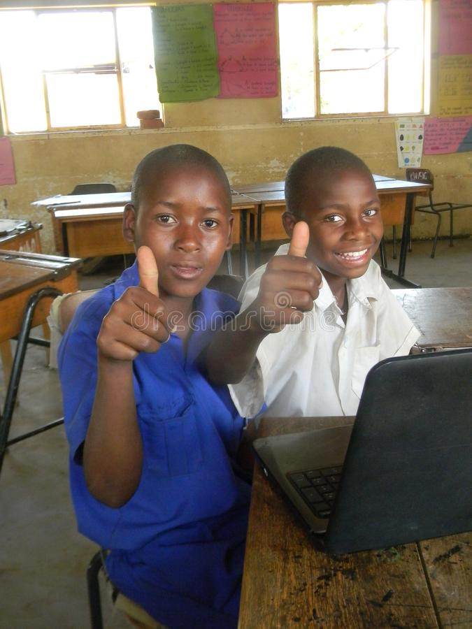 Two African school children with laptop showing thumbs-up stock photos