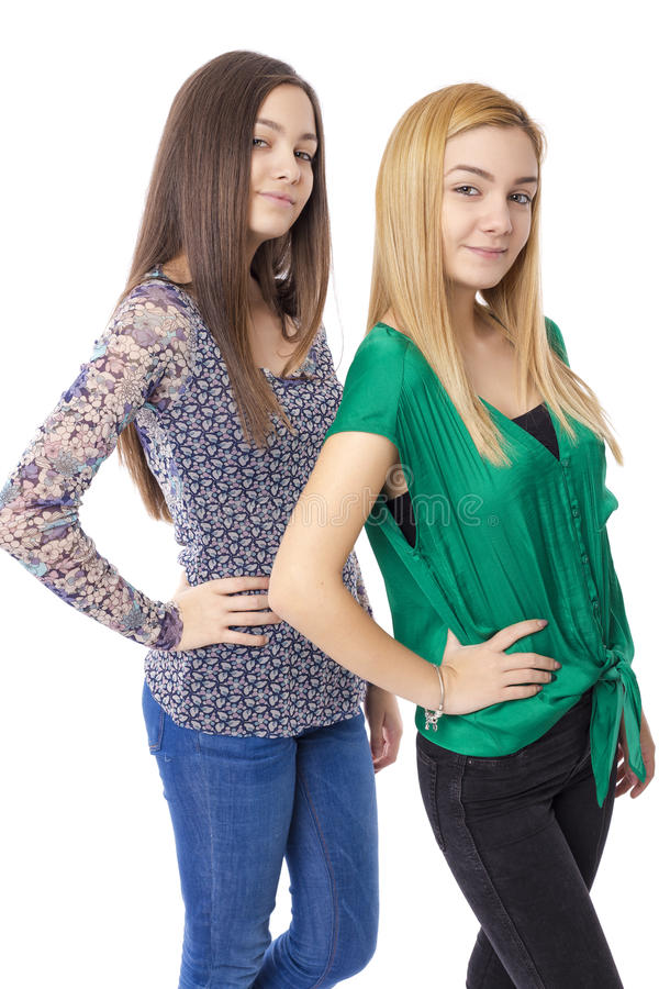 Two smiling attractive teenage girls - blond and brunette-posing. On white background stock photo