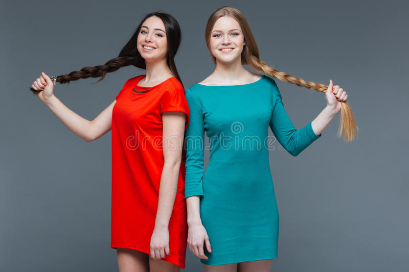 Two smiling beautiful women standing and showing their long braids royalty free stock photos
