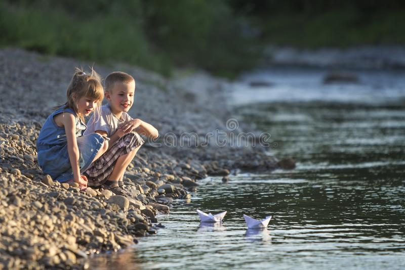 Two smiling blond children, boy and girl playing with white paper boats on river bank on bright summer blurred blue background. J stock image
