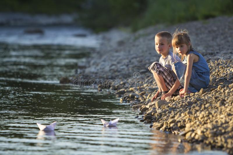 Two smiling blond children, boy and girl playing with white paper boats on river bank on bright summer blurred blue background. J stock photo