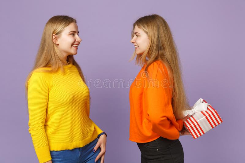 Two smiling blonde twins sisters girls in vivid clothes hold red striped present box with gift ribbon  on violet stock photo