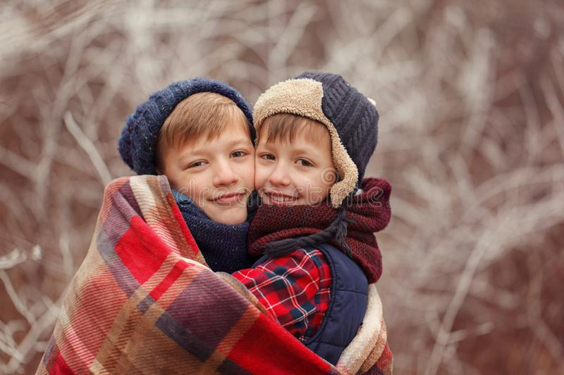 Two smiling brothers hugging each other covered with a warm blanket on a winter day. stock images