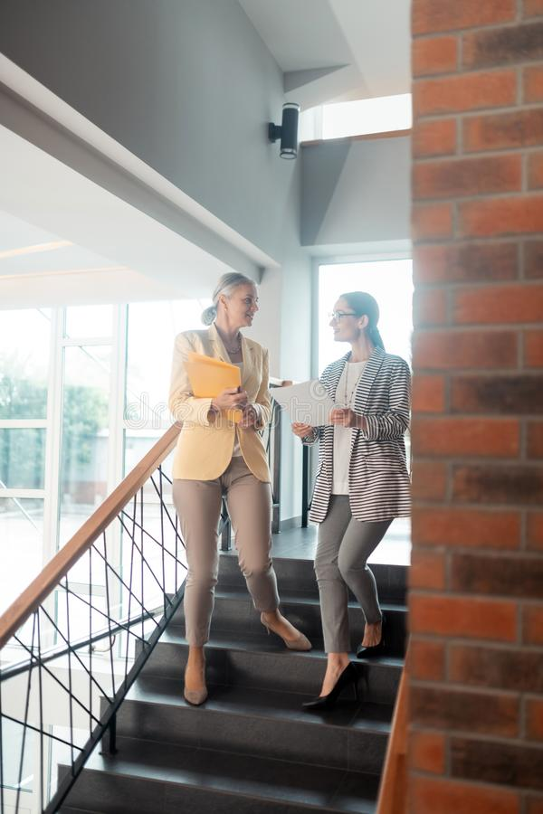 Free Two Smiling Business Ladies Going Down The Stairs Stock Photography - 156537032
