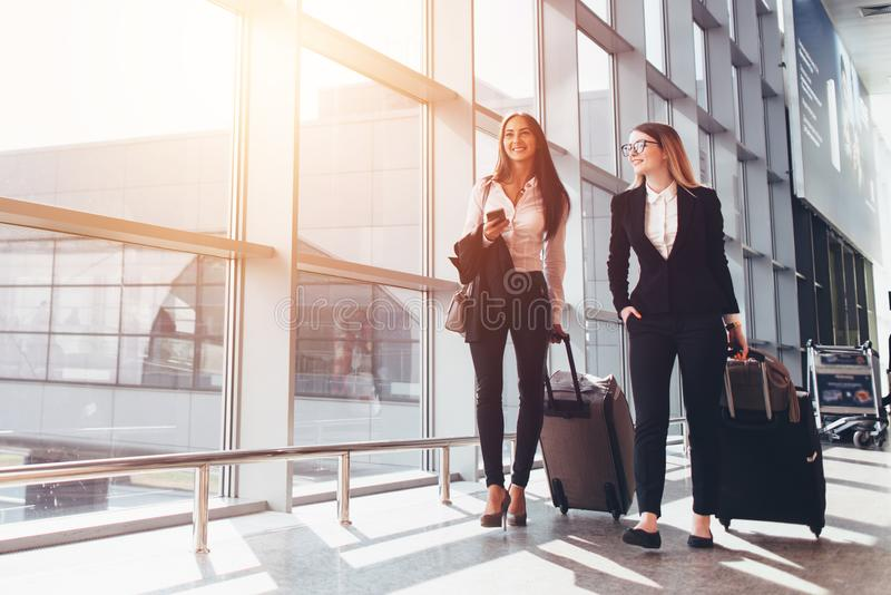 Two smiling business partners going on business trip carrying suitcases while walking through airport passageway royalty free stock photography