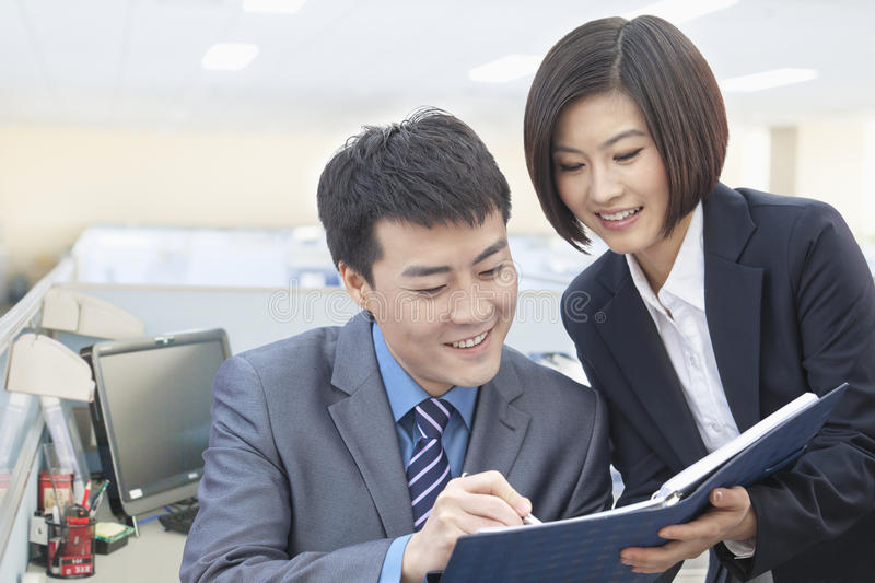 Download Two Smiling Business People Looking Down At Note Pad And Working Together Stock Photo - Image of digital, chinese: 31108010