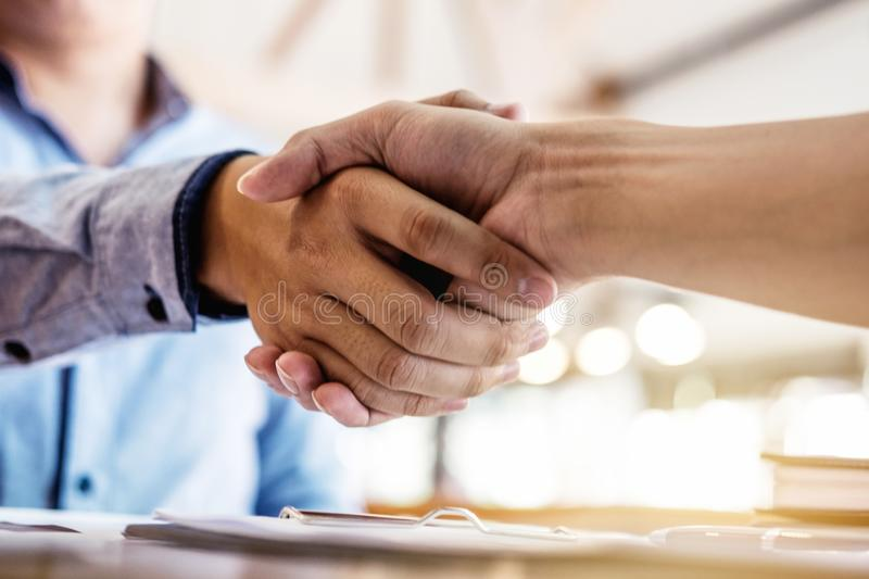 Two smiling businessman shaking hands together after good deal c. Onnection to join investment business royalty free stock image