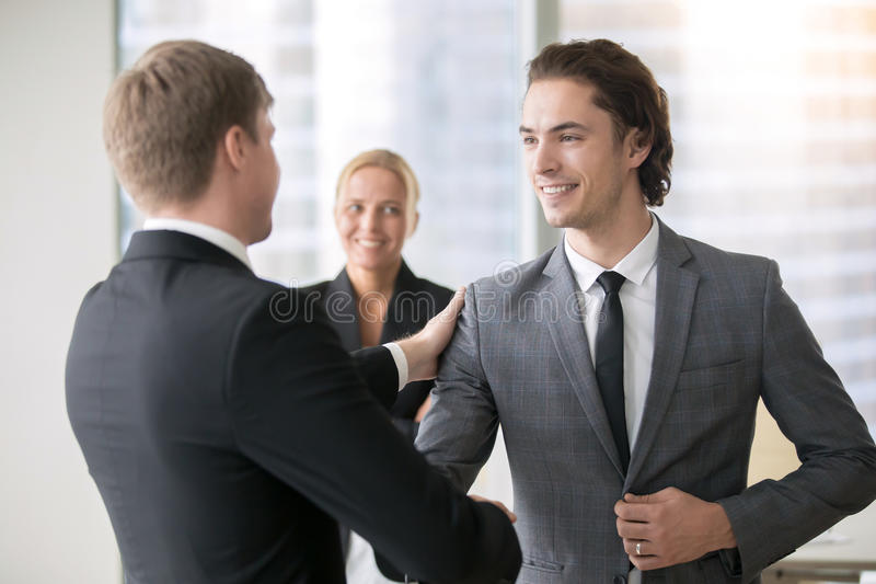 Two smiling businessmen handshaking. Boss promoting male subordinate. Two businessmen handshaking, congratulating on promotion, hired young consultant, promising royalty free stock photo
