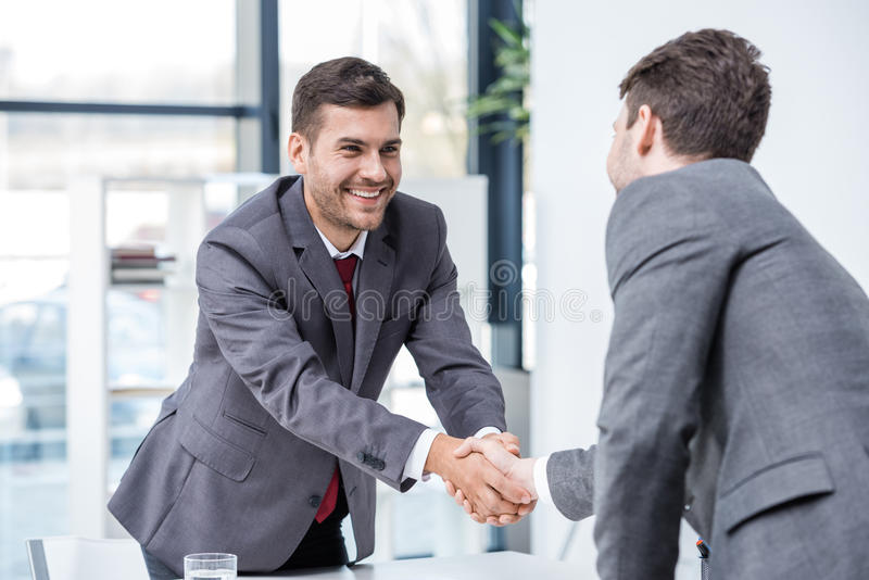 Two smiling businessmen shaking hands at meeting in office stock photo